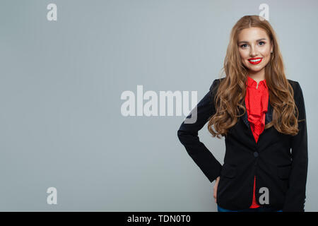 Happy woman student on gray background. Business woman in black suit portrait - Stock Image