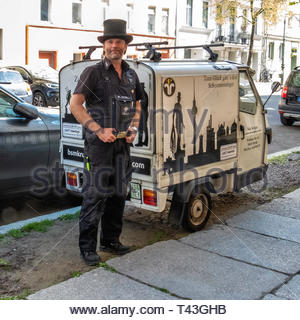 Berlin Mitte Chimney sweep in top hat with three wheeled vehicle. The Modern German sweep also inspects heating systems for energy efficiency, safety - Stock Image