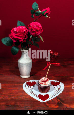 Beautiful pink roses in a vase, heart shapped white dollie with a decorated cup cake on it with a heart on a pick. - Stock Image