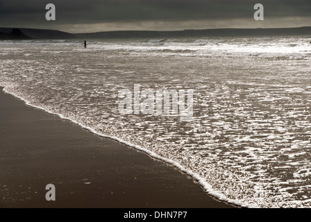 A person  in the sea at Newgale sands in South  West wales with sunlight glinting of the sea and overcast clouds behind. - Stock Image