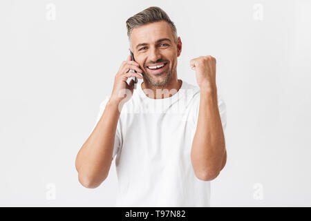 Image of happy man 30s wearing casual t-shirt holding smartphone and having mobile conversation isolated over white background - Stock Image