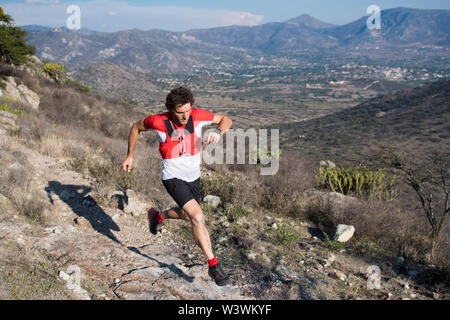 A strong athletic man jumps over rocky terrain as he goes for a trail run at the desertic landscape of El Arenal, Hidalgo, in central Mexico. - Stock Image