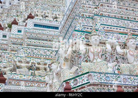 White Yaksha and dancer statues in Wat Arun temple in Bangkok, Thailand. The demon-gods statues are a common sight in Buddhist temples in Thailand, bu - Stock Image