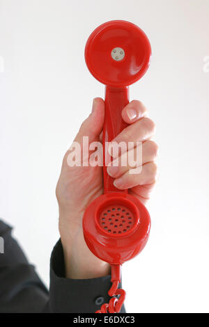 Man's hand holding old red telephone receiver. - Stock Image