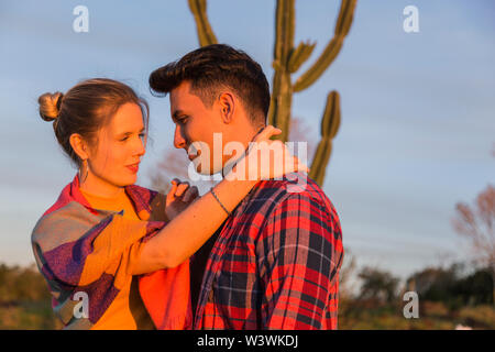 A couple enjoys the sun, with winter clothes in the golden hour and with a cactus in the background - Stock Image