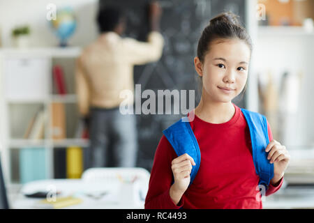 Cute schoolgirl with blue backpack looking at you in classroom on the first day of school year - Stock Image