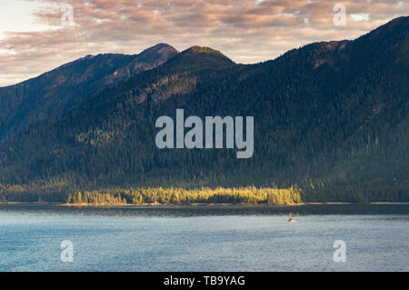 Small fishing troller in distance below mountains, early morning in Clarence Strait, North of  Ketchikan, Alaska. - Stock Image