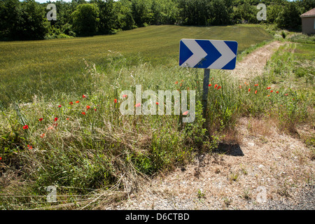 Blue chevron road-sign pointing to the right indicating a bend in road, in France, track leading away to right.Sunny - Stock Image