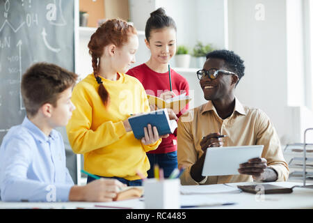 Group of pupils with books or dictionaries and pencils standing by their teacher with tablet while discussing new words - Stock Image