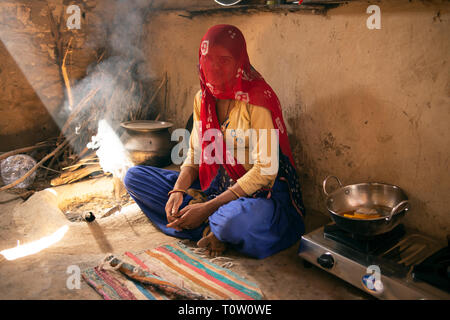 A veiled Muslim woman sits in her house by the fire. Kakani village, Jodhpur, Rajasthan, India. - Stock Image