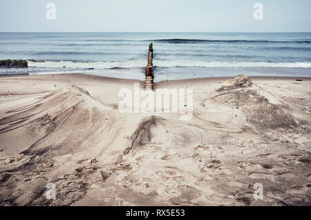 Color toned picture of a sandy beach with wooden groin. - Stock Image