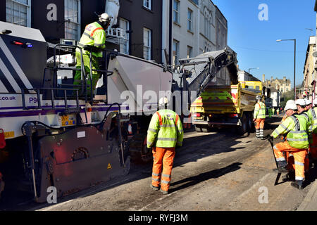 Road resurfacing works, removing old tarmac road surface with road planing machine for resurfacing, England, UK - Stock Image