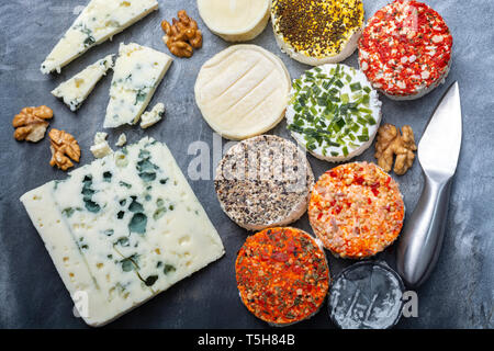 Colorful assortment of French fresh white soft goat cheeses with different tastes topping made with herbs, paprika, indian curry, bruscetta, chives an - Stock Image