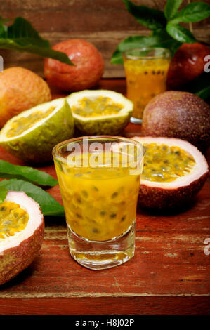 Passion fruits with leaves on wooden background - Stock Image