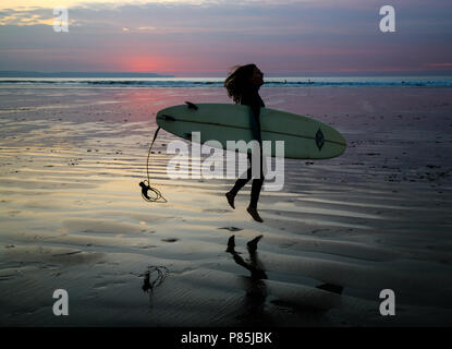 Young surfer jumping for joy with her board as she heads off evening surfing at Westward Ho! beach, North Devon, England, Europe. - Stock Image
