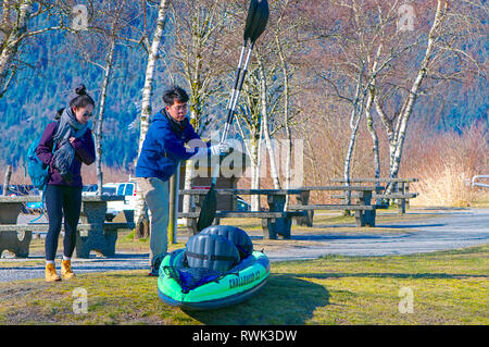 Young Asian couple with their inflatable kayak and paddles in the picnic area of Grant Narrows Regional Park, B.C., Canada - Stock Image