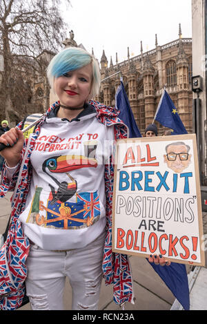 London, UK. 15th January 2019. EU Supergirl Madeleina Kay (Alba White Wolf) holds a poster 'All Brexit Positions Are Bollocks! Groups against leaving the EU, including SODEM, Movement for Justice and In Limbo and Brexiteers Leave Means Leave and others protest opposite Parliament as Theresa May's Brexit deal was being debated.  While the two groups mainly kept apart, a small group, some in yellow jackets came to shout insults at pro-EU campaigners, while police tried to keep the two groups separate. Credit: Peter Marshall/Alamy Live News - Stock Image