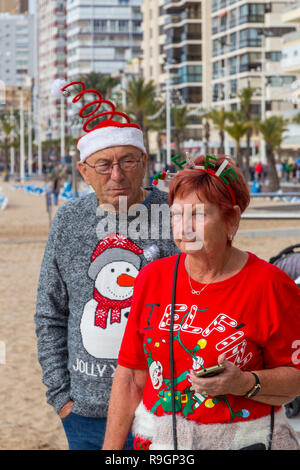 Benidorm, Costa Blanca, Spain, 25th December 2018. British tourists dress for the occasion on Christmas Day in this favourite getaway destination for Brits escaping the cold weather at home. Temperatures will be in the mid to high 20's Celsius today in this mediterranean hotspot Middle aged couple wearing Christmas Jumpers walking outside on the sea front promenade on Levante Beach. - Stock Image