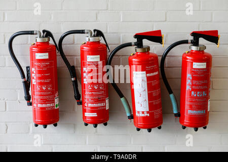 31.03.2019, Hannover, Lower Saxony, Germany - Four red fire extinguishers on a wall at the Hannover Fair. 00X190331D040CAROEX.JPG [MODEL RELEASE: NO,  - Stock Image