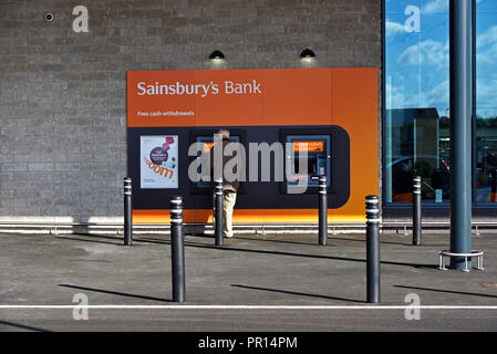 Sainsbury's Bank. Free cash withdrawals. Customer at ATM cashpoint. Sainsbury's  and Argos Supermarket. Shap Road, Kendal, Cumbria, England. - Stock Image