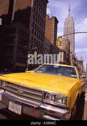 Yellow cab and Empire State building Manhattan New York USA - Stock Image