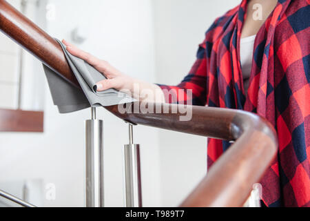 Woman polishes wooden stairs handrail with grey cloth. - Stock Image
