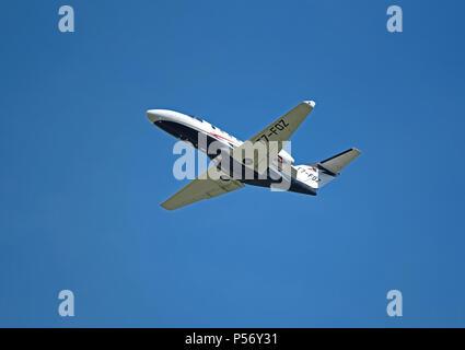 San Marino registered Cessna 525 Citation Jet/m2  T7-FOZ departs Inverness Dalcross airport into clear blue sky. - Stock Image