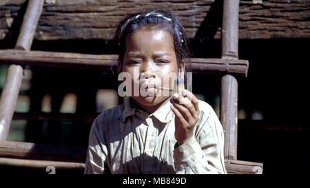 A young ethnic Kreung girl demonstates how young girls like her used to smoke pipes. This custom is now almost eliminated in such Cambodian societies. - Stock Image