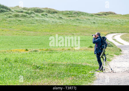 A birdwatcher scanning the machair on South Uist for corncrakes, Crex crex. - Stock Image