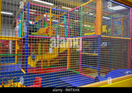 Abstract of children's soft play area seen through protective mesh - Stock Image