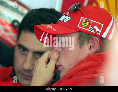 Finnish Formula One driver Kimi Raikkonen of Ferrari gestures converses in the garage after the third practice sessiont - Stock Image