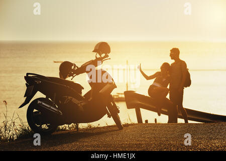 Happy couple sunset sea motorcycle road - Stock Image