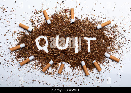 An Elevated View Of Frame Made With Broken Cigarettes Around Quit Word Written On Tobacco - Stock Image