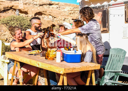 Group of people young men and women toasting together with beers in friendship outdoor leisure activity - alternative camping summer holiday vacation  - Stock Image