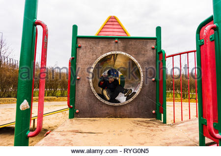 Poznan, Poland - March 3, 2019: Young boy with bike safety helmet sitting in a tunnel of a climb equipment at a public playground in a park on a cloud - Stock Image