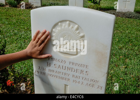 A hand caresses the memorial to  Australian aboriginal soldier, Harry Saunders at Bomana War Cemetery in Port Moresby, - Stock Image