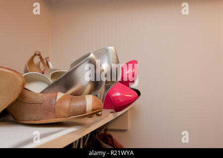 Silver, pink and brown shoes on the top sheld of a closet - Stock Image