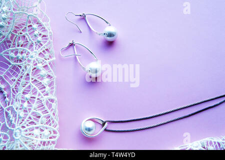 Beautiful silver shiny pearl jewelry with trendy neon glow, trendy glamorous earrings, chain on pink purple background with exquisite lace. Flat lay,  - Stock Image