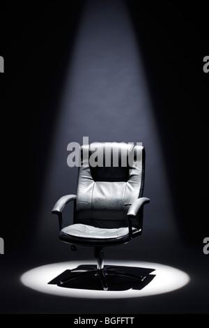 Empty Black Leather Chair under Spotlight Mastermind - Stock Image