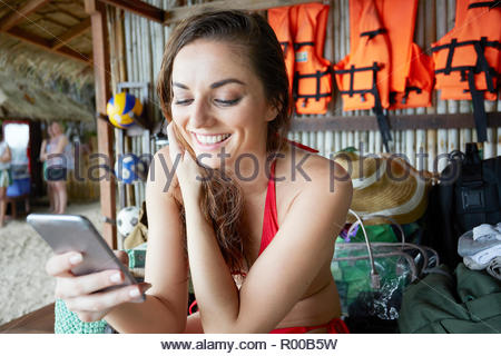 Young woman holding mobile phone while smiling - Stock Image