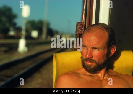 Train hobo and photographer Chad Ehlers riding the rail in box car across the plains of Montana - Stock Image