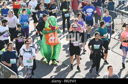 Brighton, UK. 24th Feb, 2019. A runner in a dinosaur costume taking part in the Grand Brighton Half Marathon on a beautiful sunny morning . Over 13000 runners were expected to take part in aid of the Sussex Beacon charity Credit: Simon Dack/Alamy Live News - Stock Image