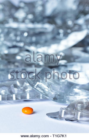 One single pill in front of many empty blister packages on white background, drug misuse concept - Stock Image