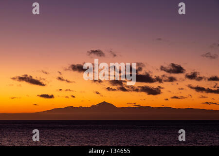Mount Tiede on Tenerife in silhouette at  dusk from Puerto de Las Nieves on Gran Canaria in the Canary Islands - Stock Image
