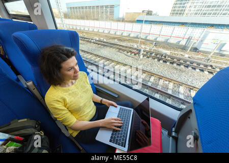 young woman loking in window and thinking what write in laptop during her traveling in train - Stock Image