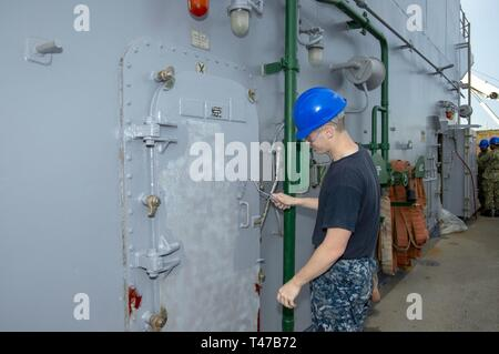 Fla. (Mar. 11, 2019) Fire Controlman 3rd Class Avery Doyle, from Allen Park, Mich., paints a quick acting water tight door aboard the Wasp-class amphibious assault ship USS Iwo Jima (LHD 7), Mar 11, 2019. Iwo Jima is currently at her homeport conducting Chief of Naval Operations Maintenance Availability. - Stock Image