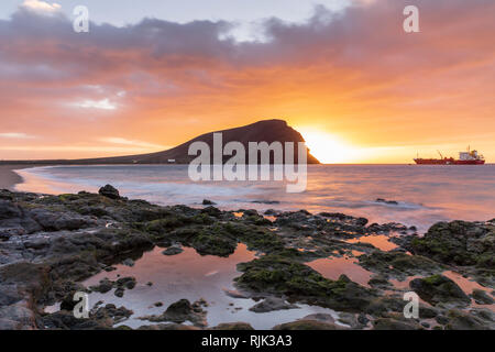 Tanker ship moored at dawn by Montana Roja, Red mountain, at Playa de Tejita at sunrise on the east coast of Tenerife, Canary Islands, Spain - Stock Image