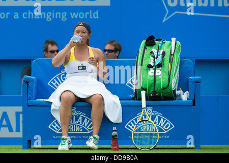 British tennis player Tara Moore takes a drink during the break between games on a blue bench with a towel over - Stock Image