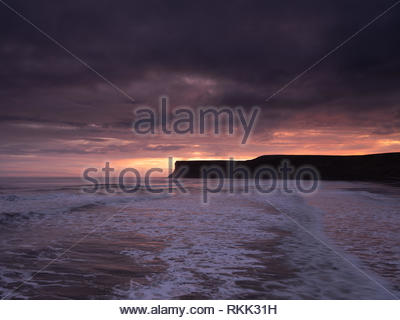 Saltburn-by-the-Sea. 12th Feb 2019. Weather: Sunrise on the coast at Saltburn-by-the-Sea on the north-east coast with Hunt Cliff  silhouetted by the sunrise. 12th February 2019. © Gary Clarke/Alamy Live News - Stock Image