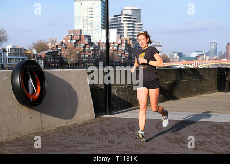 A young woman running by the River Thames in Battersea Wandsworth London England UK  KATHY DEWITT - Stock Image